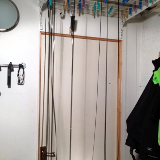 Once washed, the film is unwound from its temporary spool and hung from the drying rack in loops.